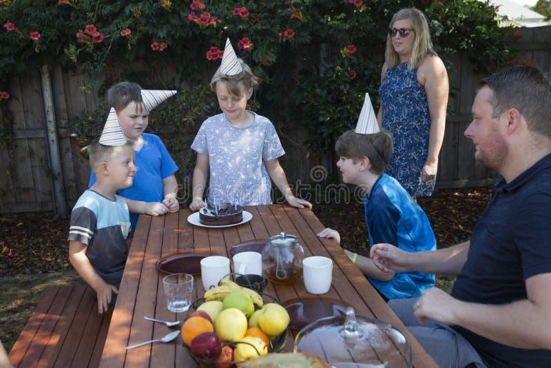 En familj firar ett barns födelsedag utomhus royaltyfri foto