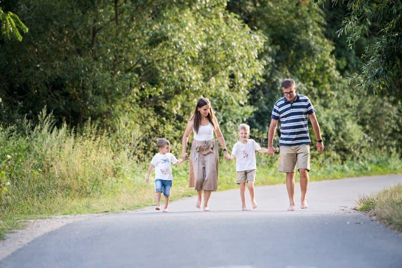 En familj med två lilla söner som barfota går på en väg i, parkerar på en sommardag arkivfoto