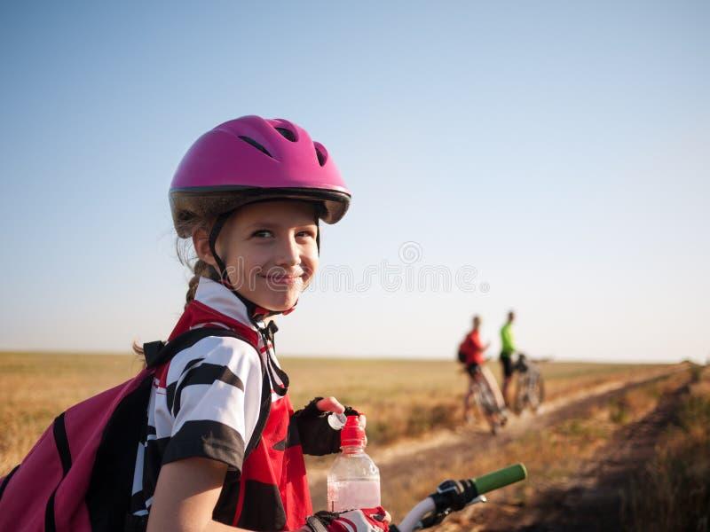 Familj som utomhus cyklar royaltyfria bilder