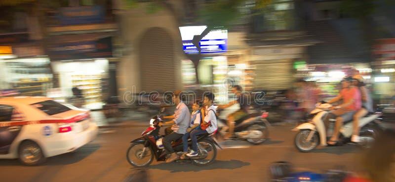 En familj som tillsammans rider på en cykel i natten Hanoi arkivbild