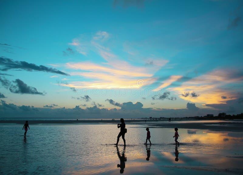 En familj som tycker om en dramatisk blå solnedgång royaltyfri fotografi