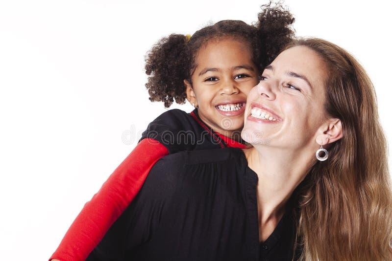 En familjmoder med flickabarnet som poserar på en vit bakgrundsstudio arkivbilder