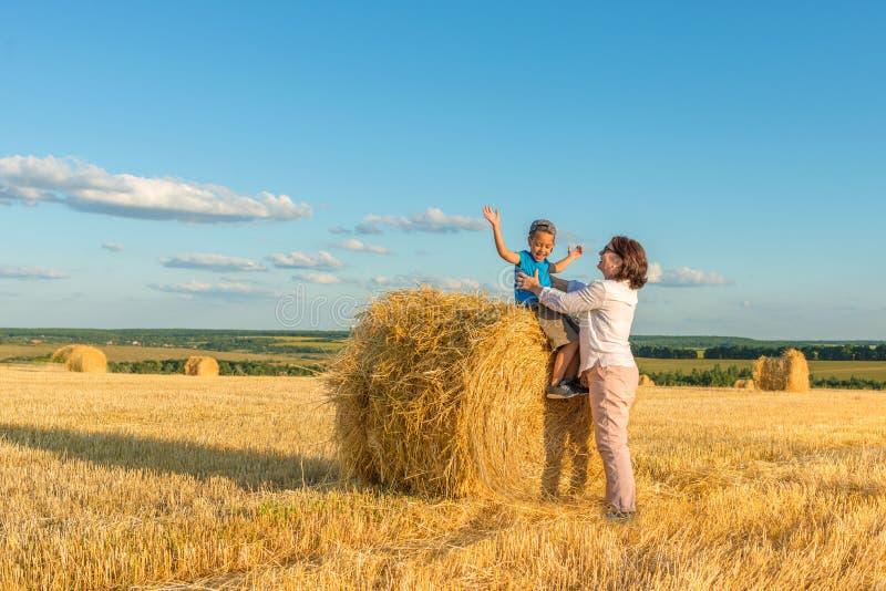 En farmor med en sonson sätter på en höstack på ett fält på en solig dag Den gladde sonsonen, har de gyckel tillsammans arkivfoton