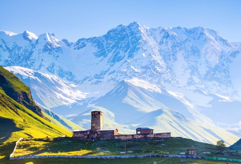 En fascinerande sikt på den Ushguli byn på foten av snö-korkad Mt Shkhara arkivbild