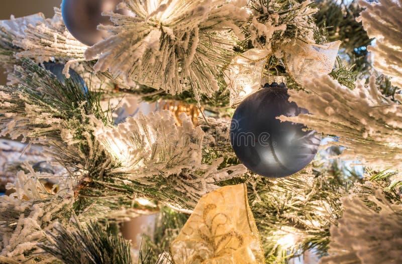 En fast blå julprydnad på en flockas julgran royaltyfri bild