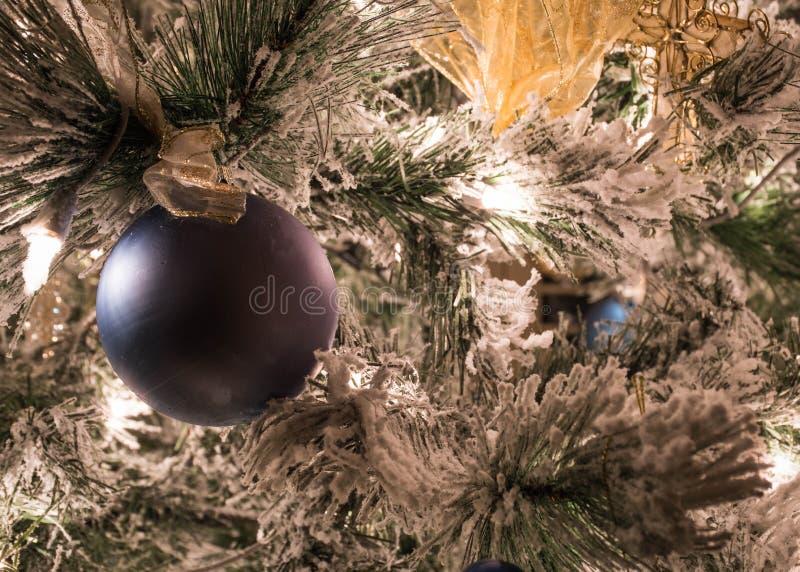 En fast blå julprydnad på en flockas julgran arkivbild