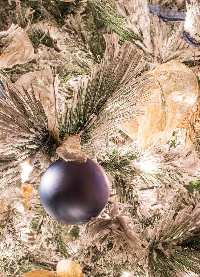 En fast blå julprydnad på en flockas julgran arkivfoton