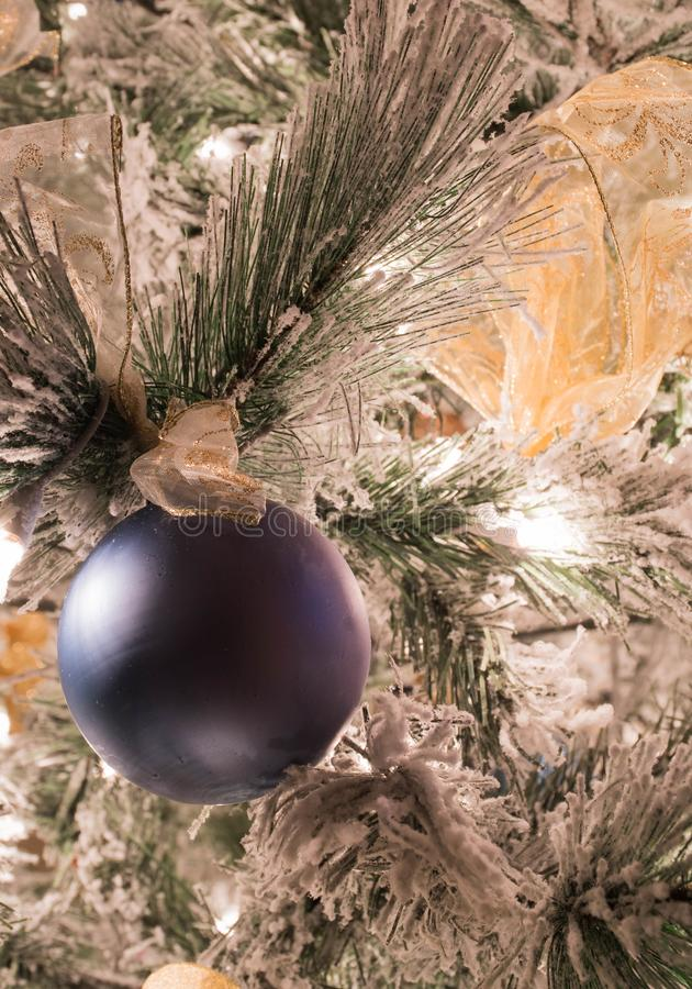 En fast blå julprydnad på en flockas julgran royaltyfri fotografi