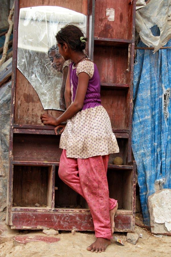 En fattig flicka som ser i en spegel från en stads- slumkvarter i New Delhi royaltyfri foto