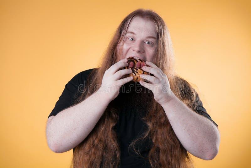 En fet man biter en stor söt kaka royaltyfria bilder
