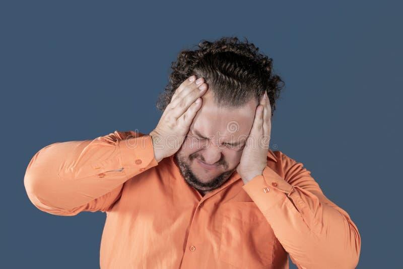 En fet man har hög blodtryck och huvudvärk Övervikt och hälsoproblem arkivbilder