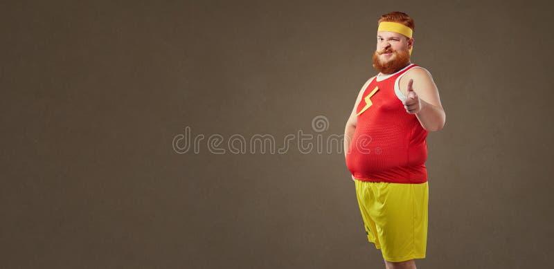 En fet man med ett skägg i en träningsoverall royaltyfria bilder