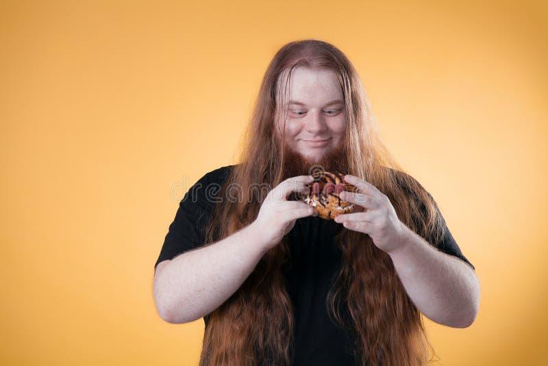 En fet rödhårig man rymmer en stor läcker kaka fotografering för bildbyråer