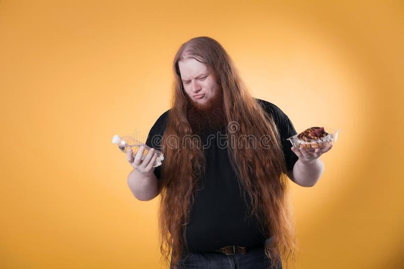 En fet rödhårig man rymmer vatten och en kaka royaltyfri foto