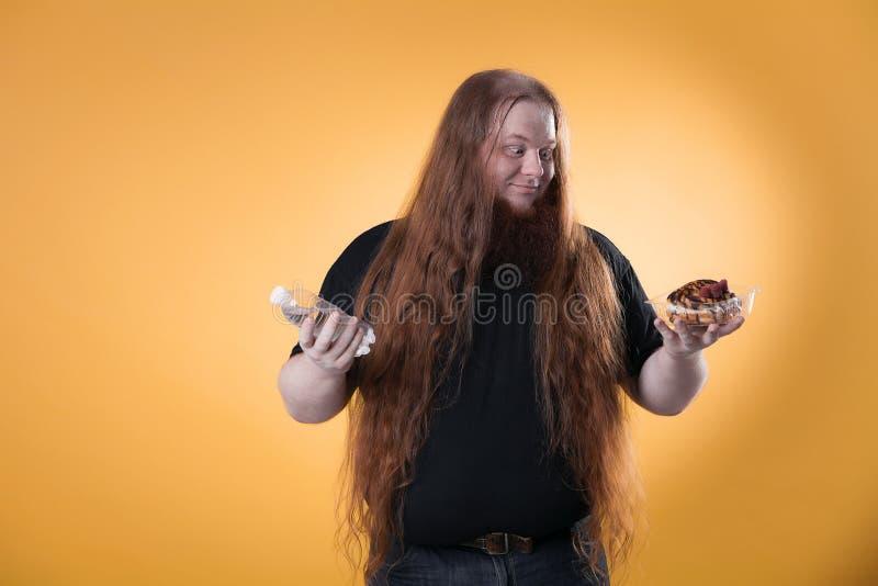 En fet rödhårig man rymmer vatten och en kaka arkivfoton