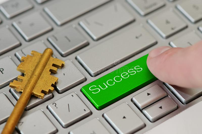 En fingerpress en grön knapp med textframgång på bärbar datortangentbordet royaltyfria bilder