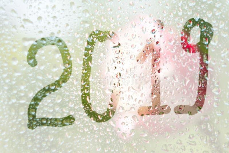 En fingerteckning av formen av banden av numret 2019 på ett semitransparent misted exponeringsglas regndroppar av vårregn på arkivbilder