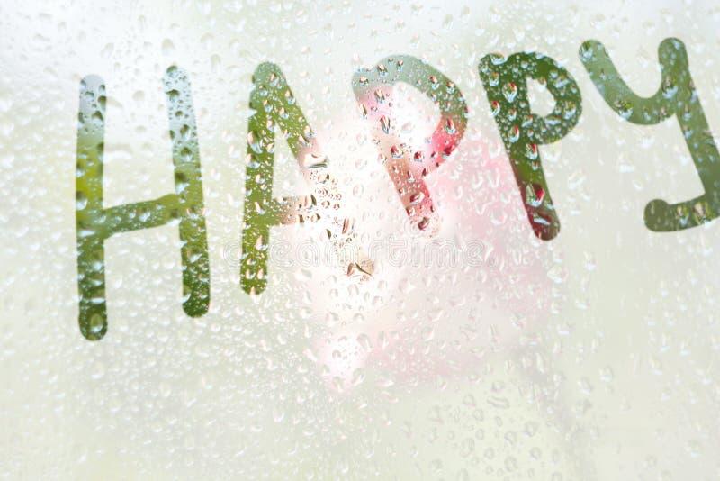 En fingerteckning av formen av bandet av ordet som är lyckligt på ett semitransparent misted exponeringsglas regndroppar av vårre royaltyfria bilder