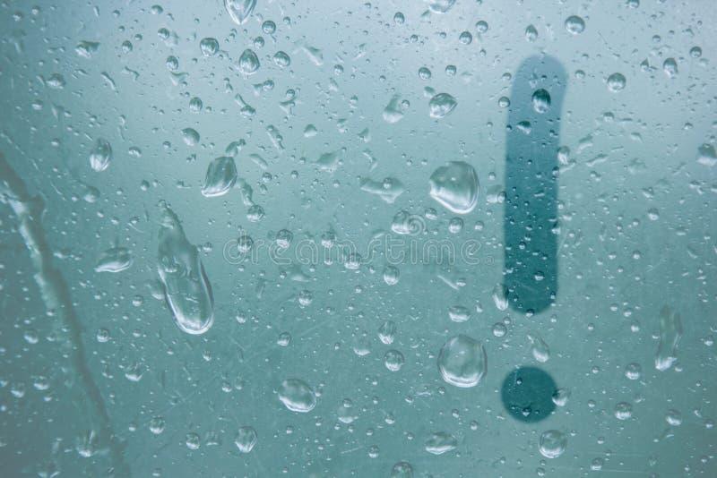 En fingerteckning av formen av ett utropsteckenband på ett semitransparent dimmigt exponeringsglas regndroppar av vårregn på royaltyfri bild