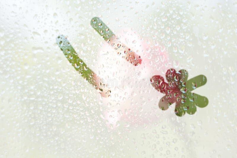 En fingerteckning av formen av en kyssande emoticonremsa på ett semitransparent misted exponeringsglas regndroppar av vårregn på arkivbilder