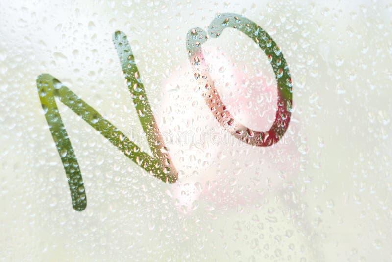 En fingerteckning av formen av remsorna av ordet inte på ett semitransparent misted exponeringsglas regndroppar av vårregn på royaltyfria foton