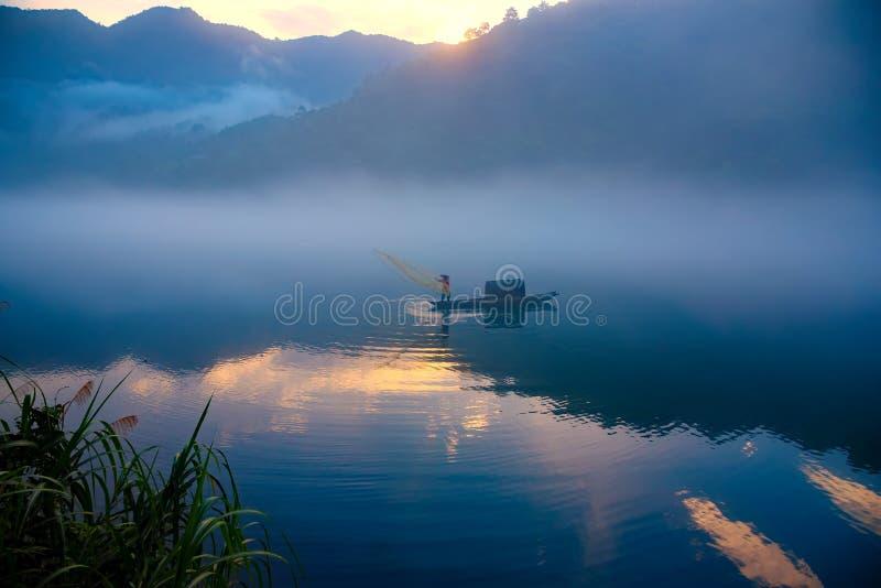 En fishman gjuter ett netto på fartyget i dimman på floden, den guld- molnreflexionen på yttersidan av vatten, på gryning royaltyfri fotografi