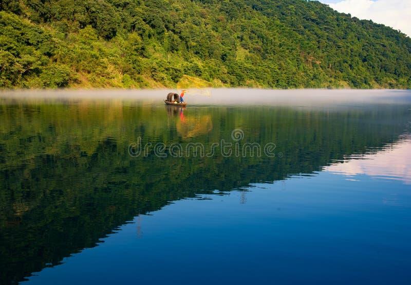 En fishman gjuter ett netto på fartyget i dimman på floden, den guld- solskenreflexionen på yttersidan av vatten royaltyfri foto