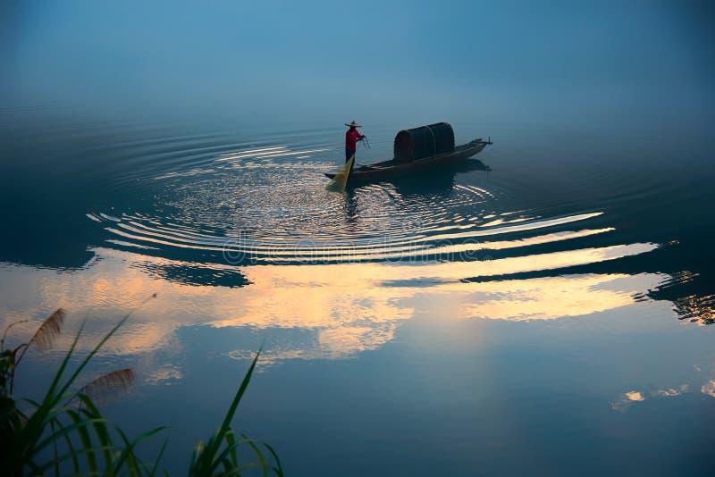 En fishman på fartyget i dimman på floden, den guld- molnreflexionen på yttersidan av floden, bliven guld- krusning P? skymning arkivbild