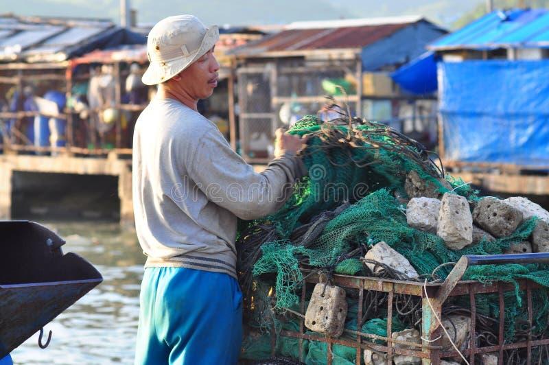 En fiskare förbereder hans fisknät för ny arbetsdagspå en lokal hamnstad arkivbild