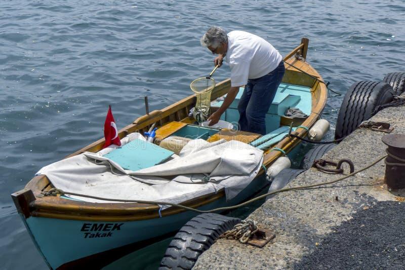 En fiskare lastar av hans lås från ett fartyg som anslutas på det guld- hornet på Istanbul i Turkiet royaltyfria foton