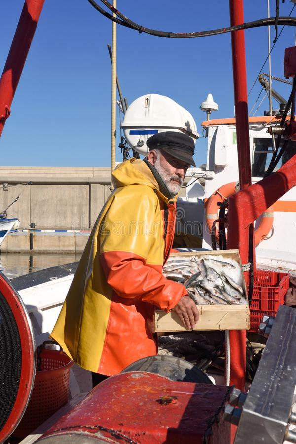 En fiskare med en fiskask inom en fiskebåt arkivbilder