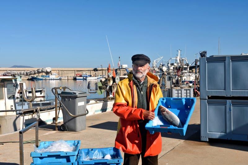 En fiskare med en fiskask inom en fiskebåt royaltyfria foton