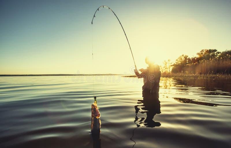 En fiskare med en metspö i hans hand och en fisk royaltyfria foton