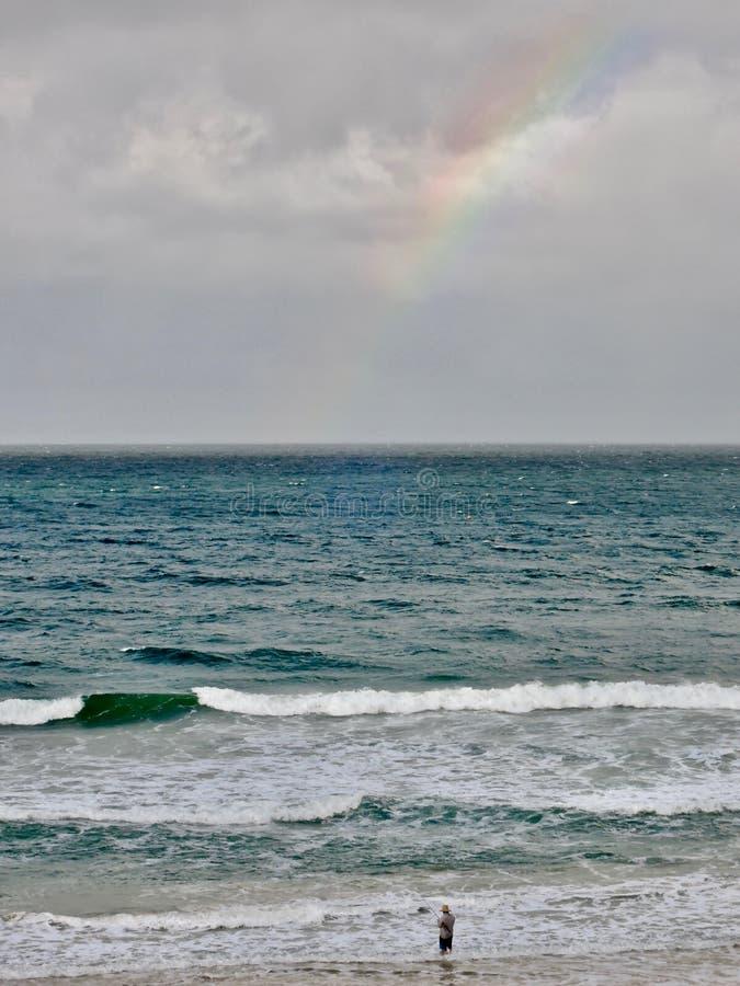 En fiskare på stranden vid regnbågestrandstaden - Queensland, Australien royaltyfria foton