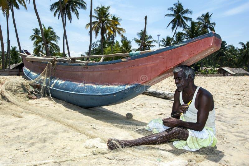 En fiskare reparerar hans förtjänar på den Arugam fjärdstranden på ostkusten av Sri Lanka royaltyfri bild