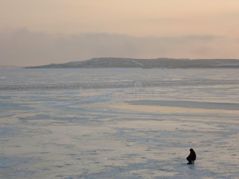 En fiskare sitter nära ishålet på den djupfrysta floden på en härlig solnedgång på en frostig dag arkivfoto