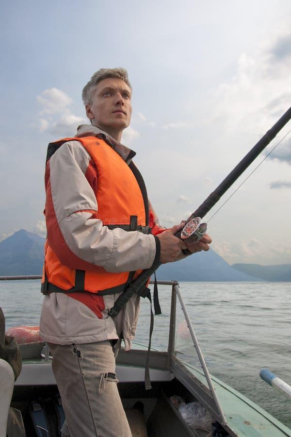 En fiskare som slitage en flytväst. arkivbild