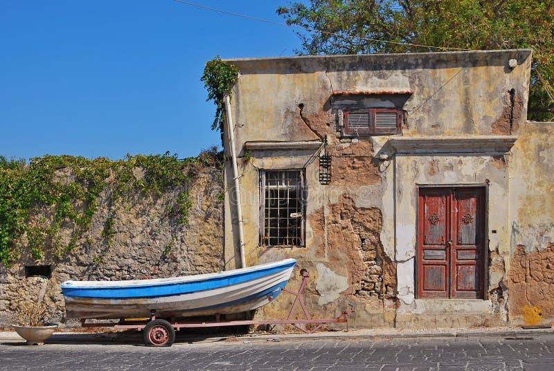 En fiskebåt på en vagn nära det gamla huset Rhodes Grekland royaltyfri bild