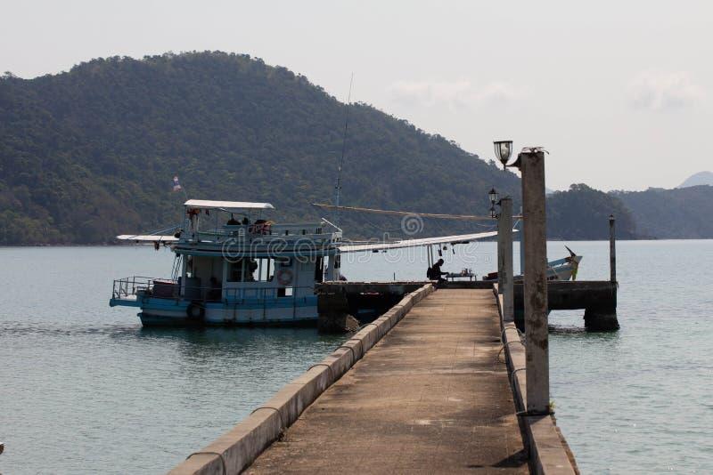 En fiskebåt som binds upp på slutet av en brygga royaltyfri foto