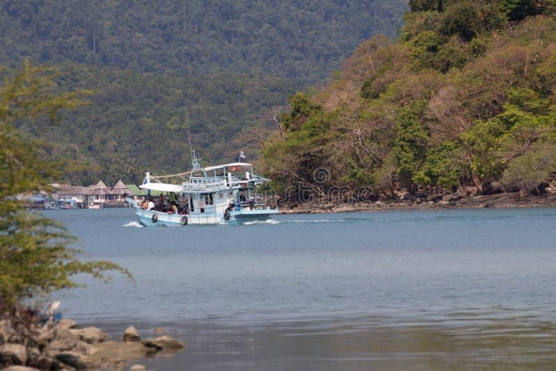 En fiskebåtsegling mellan två öar arkivfoto