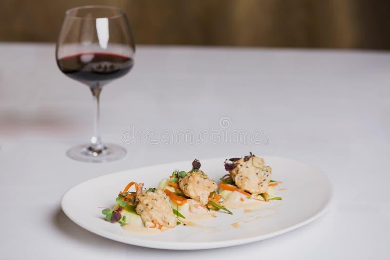 En fiskmaträtt och ett exponeringsglas av rött vin på vit bakgrund royaltyfri foto