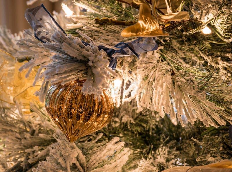 En flöjtlik guld- julprydnad på en flockas julgran royaltyfria foton