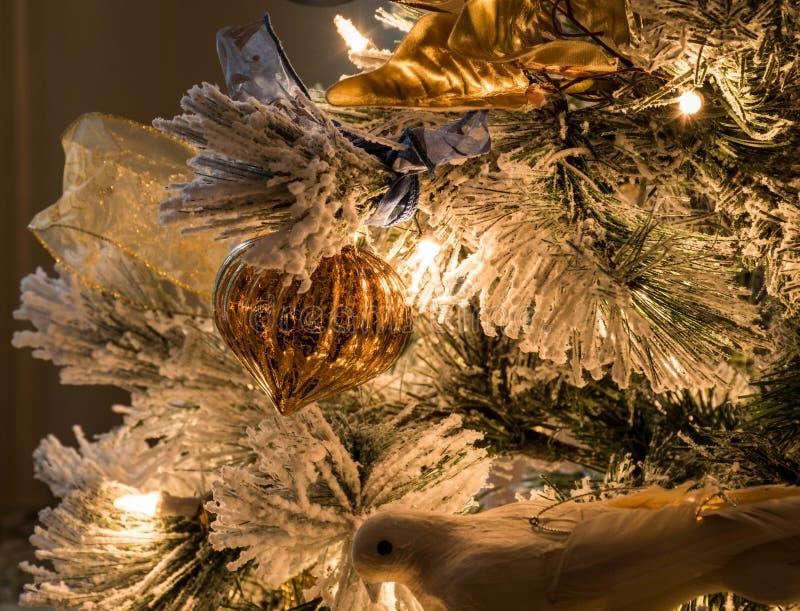 En flöjtlik guld- julprydnad på en flockas julgran royaltyfri foto