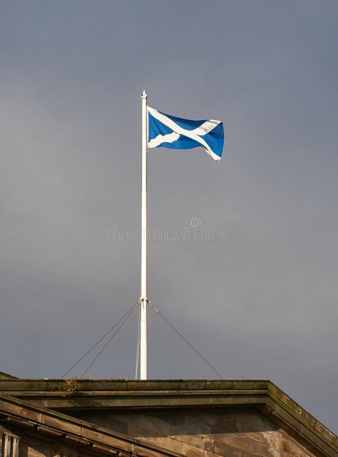 En flaggstång med en skotsk flagga på skärm på taket av en historisk byggnad i centret av Glasgow arkivbilder