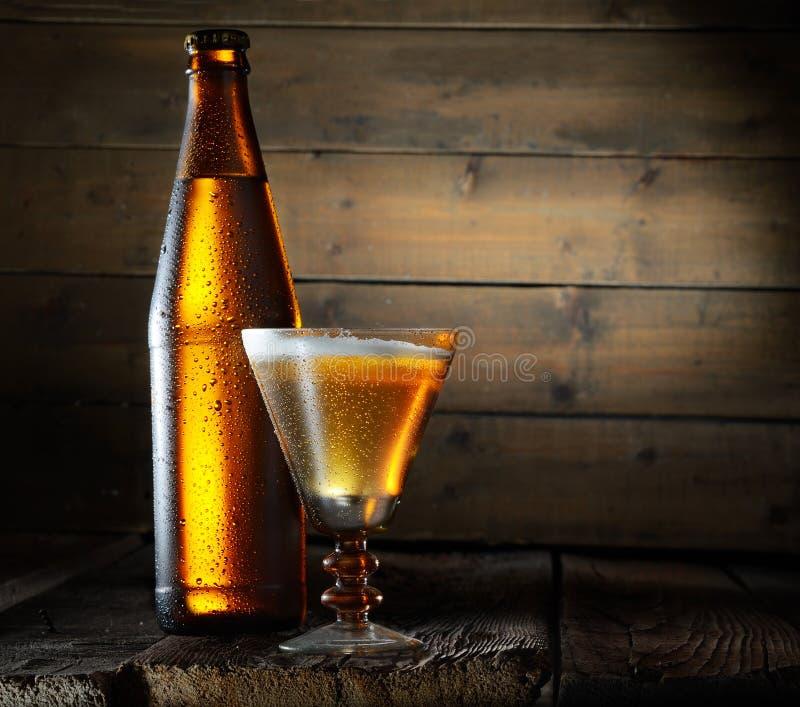 En flaska av öl och ett exponeringsglas av den original- formen med ett skummigt kallt öl på en träbakgrund arkivbilder