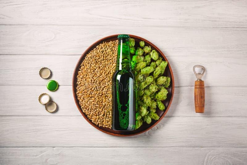 En flaska av öl på en platta med gröna flygturer och havrekorn med öppnaren och corcks på ett vitt träbräde royaltyfri foto