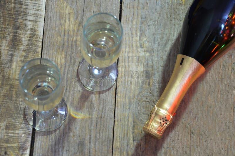 En flaska av champagne och exponeringsglas på bakgrunden av en julgran dekorerade med ljus för bollar och för ` s för nytt år fotografering för bildbyråer