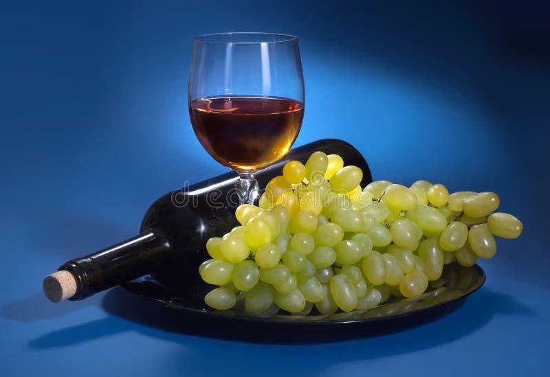 En flaska av druvavin och vita druvor på en blå bakgrund arkivbild