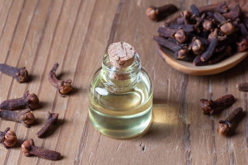 En flaska av nödvändig olja för kryddnejlika med kryddnejlikor royaltyfri foto