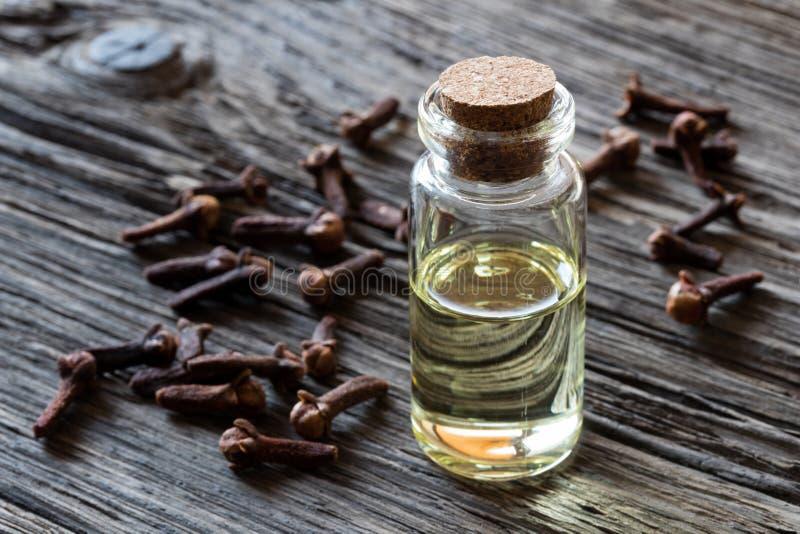 En flaska av nödvändig olja för kryddnejlika med torkade kryddnejlikor på trälodisar arkivfoto